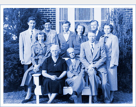 The Jennings family in front of the family's brick home, c. 1950. From left to right - Standing: Roy, Charlie, Hale, Elva, Paul, Ethel. Seated: Grace (my mother), Ollie, Fielden, Gwyn. My mother is also known as Grace Phillips and Grace Spainhour.