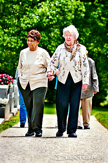 Connie Campbell and Mary Alice Warren walk together up a pathway in the graveyard at Lewisville United Methodist Church in Lewisville, NC (Forsyth County) - photographed by Deb Phillips.